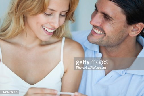 Couple looking at pregnancy test, smiling