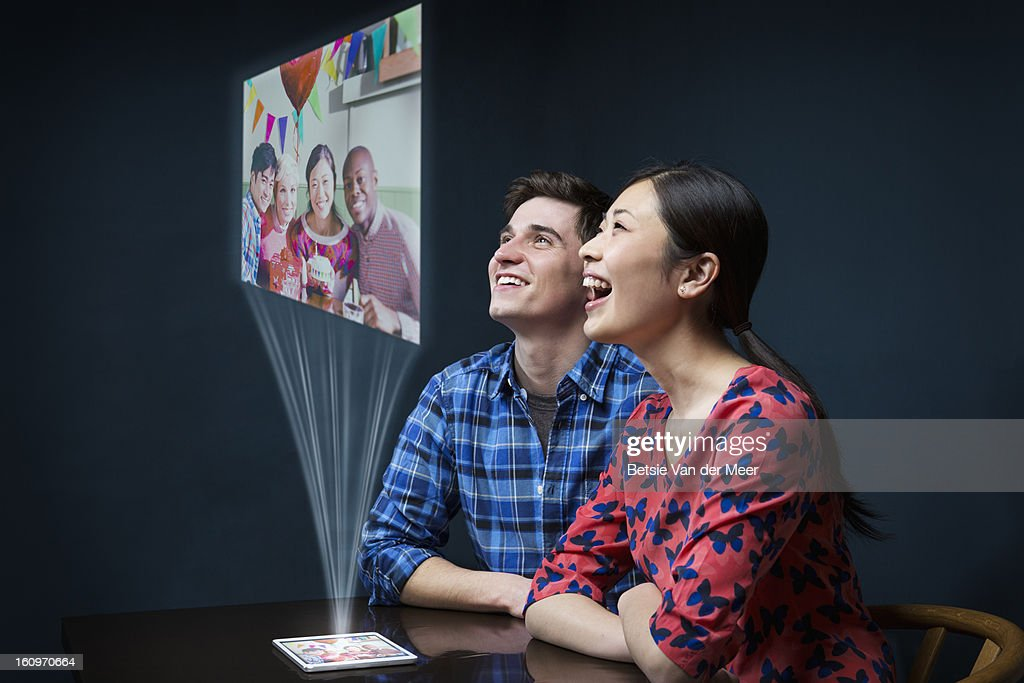 Couple looking at projected digital image... : Stock Photo