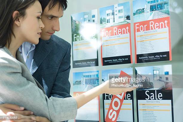 Couple looking at properties in window of real estate agency