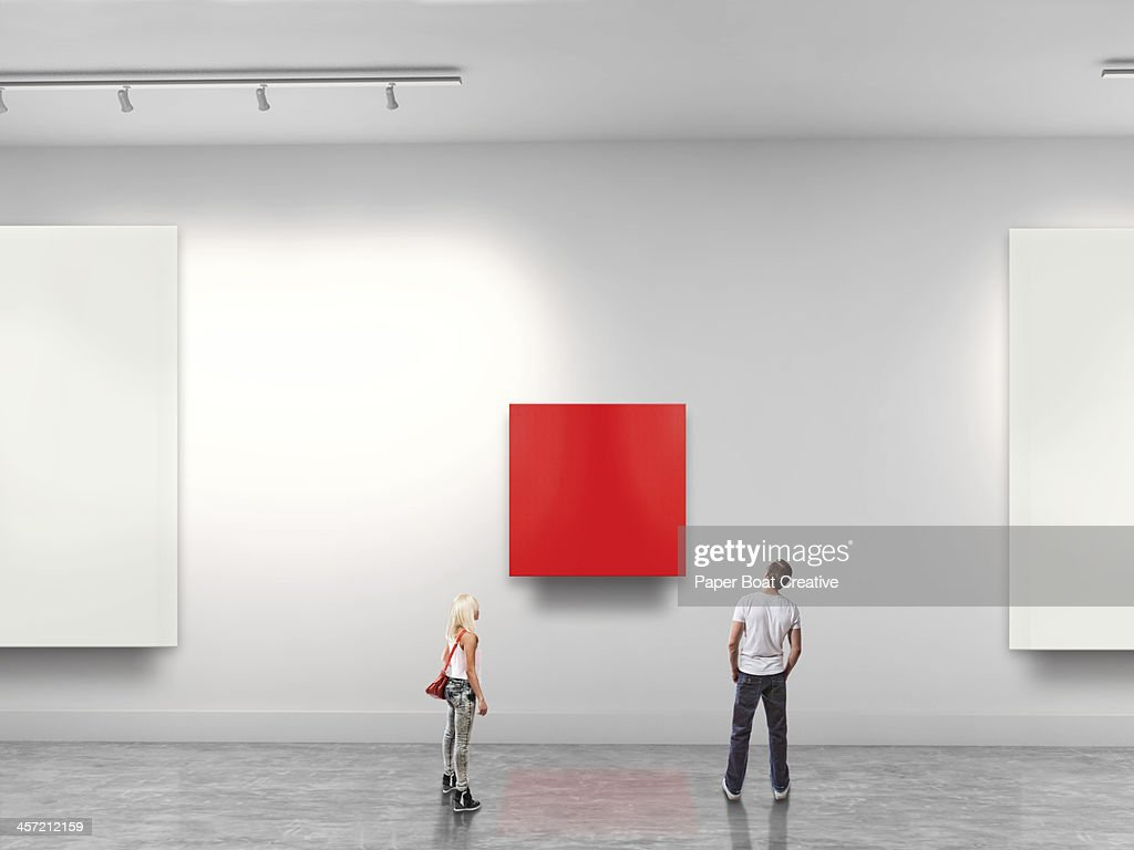 Couple looking at red blank art in gallery : Stock Photo
