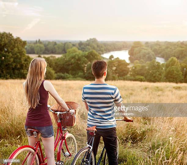 Couple looking at rural view on bikes.