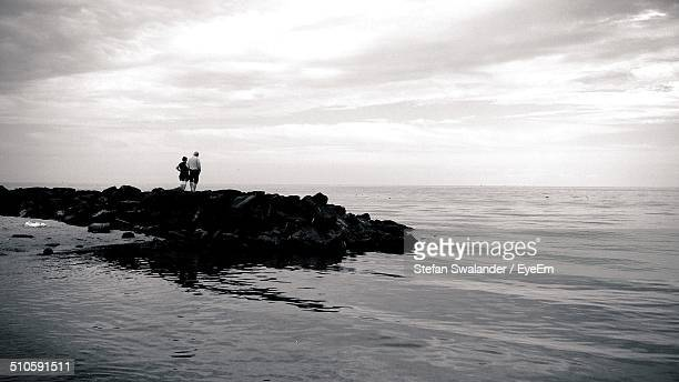 Couple looking at sea view while standing on rocks