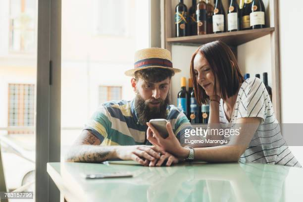 Couple looking at smartphone at bar table