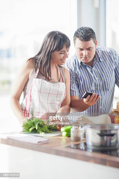 Couple looking at smartphone whilst preparing food