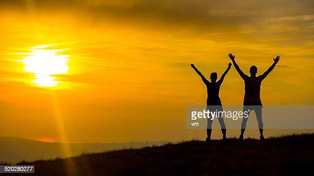 Couple à la recherche au coucher du soleil avec leurs bras en l'air