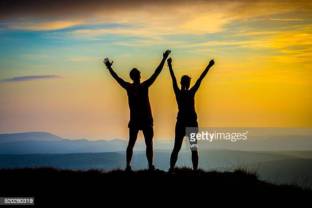 Couple Looking at Sunset With Their Arms Raised