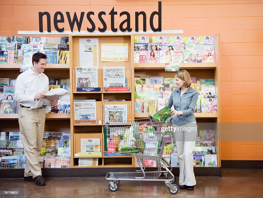 Couple Looking at Supermarket Newsstand