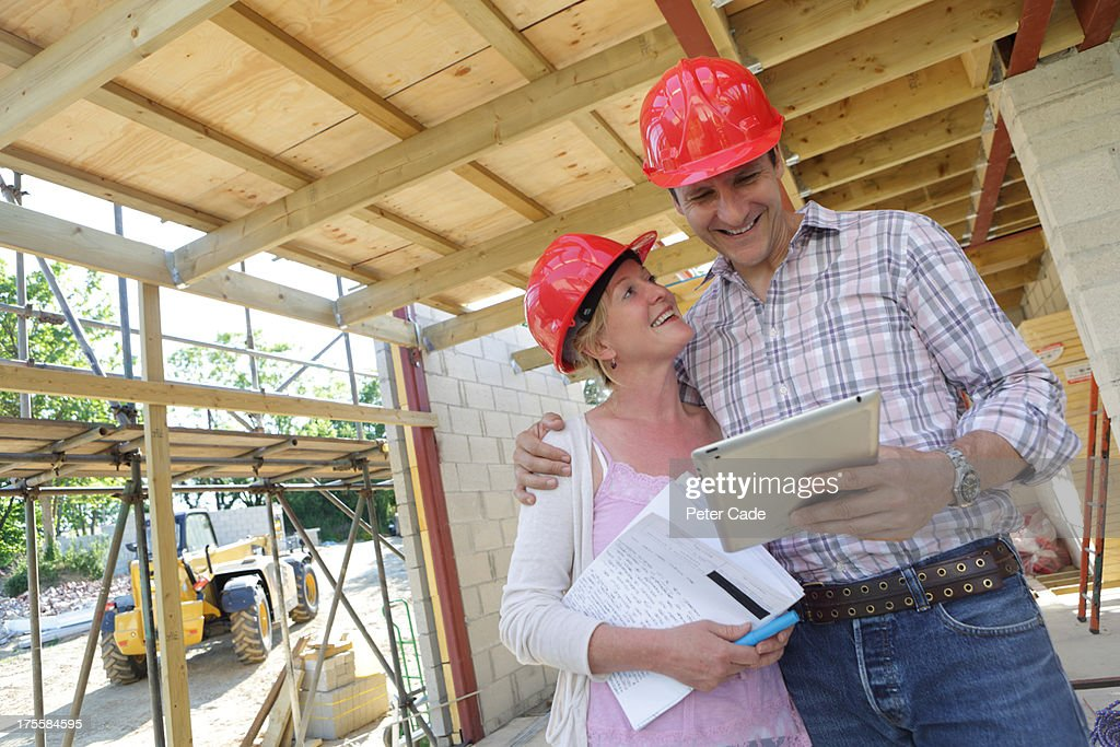 Couple looking at tablet on building site : Stock Photo