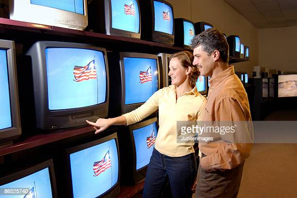 A couple looking at televisions