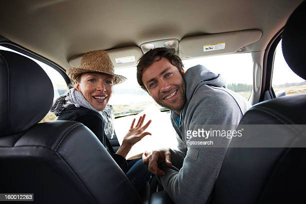 Couple looking at the back of a car