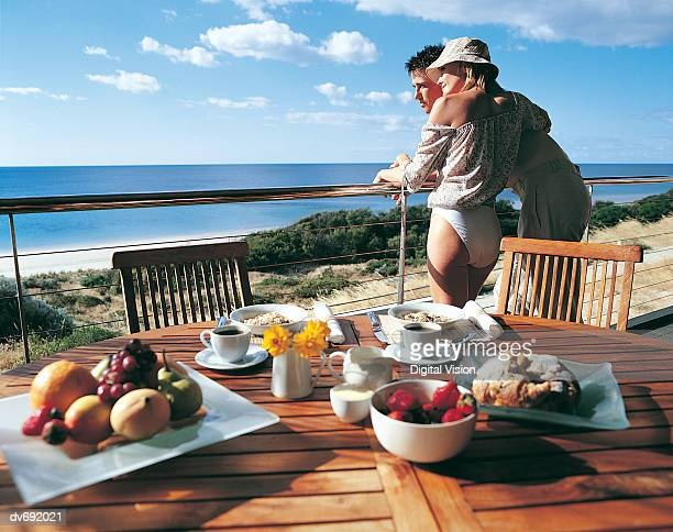 Couple Looking at the Sea with Their Breakfast in the Foreground