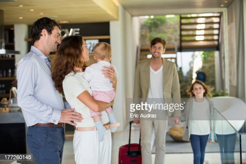 Couple looking at their friend arriving from holiday