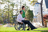 Couple looking at their neighborhood while he is in a wheelchair with a spinal cord injury