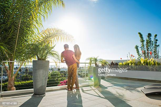 Couple looking at view from penthouse rooftop garden, La Jolla, California, USA