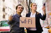 Couple looking for cell phone signal with Wi-Fi sign