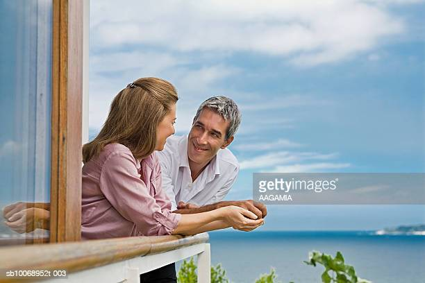 Couple looking in eyes on balcony of house at seaside