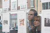 Couple Looking in Real Estate Agent's Window