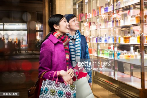 Couple looking into shopwindow in evening. : Stock Photo