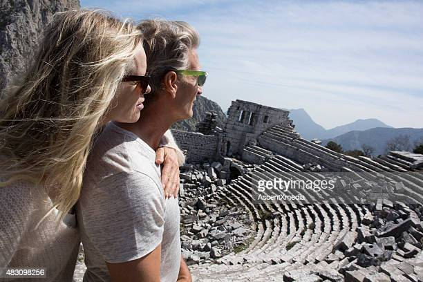 Couple looking out above theatre, ancient Greek ruin