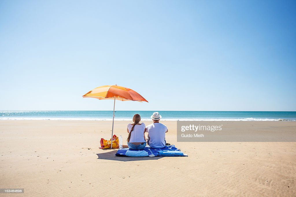 Couple looking out ocean : Stock Photo
