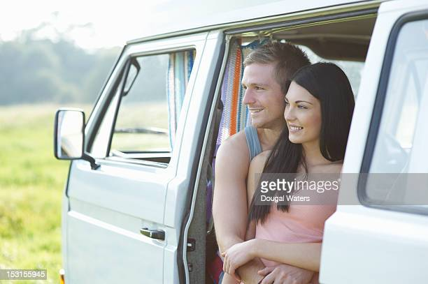Couple looking out of camper van in countryside.