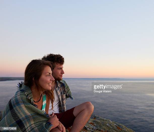 Couple looking out to sea from coastline.