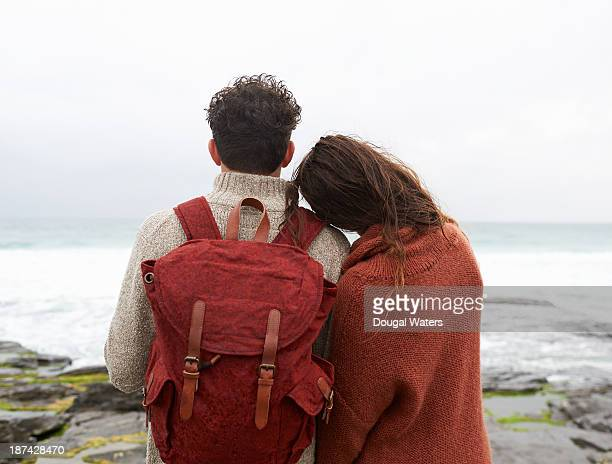 Couple looking out to sea together on UK coastline