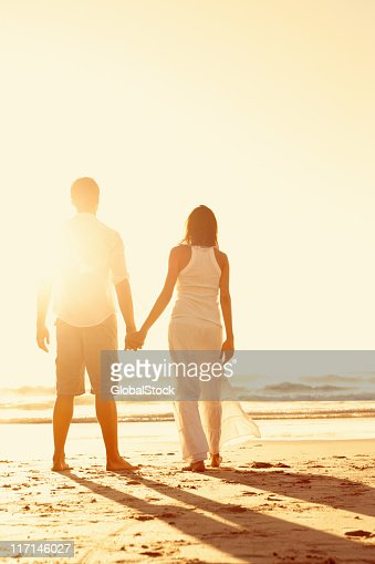 A couple looking out to the sea on a beach holding hands