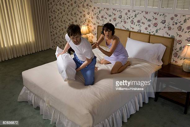 Couple looking over edge of bed nervously