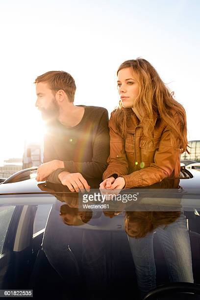 Couple looking through sunroof of a car