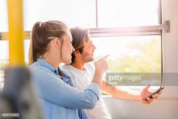 Couple looking through window while sitting in bus