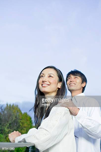 Couple looking up on balcony, smiling