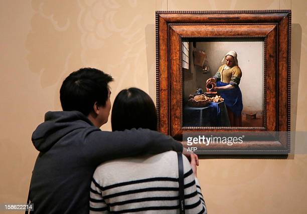 A couple looks at a famous oil on canvas painting by Dutch artist Johannes Vermeer entitled 'The kitchen maid' and dated around 1658 at the Rijks...