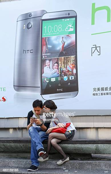 A couple looks at a mobile phone while seated in front of a billboard advertisement for the HTC Corp One M8 smartphone in Taipei Taiwan on Saturday...
