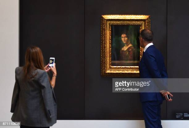 A couple looks at a painting titled 'La Belle Ferroniere' by Leonardo Da Vinci inside a gallery at the Louvre Abu Dhabi Museum during a media tour on...