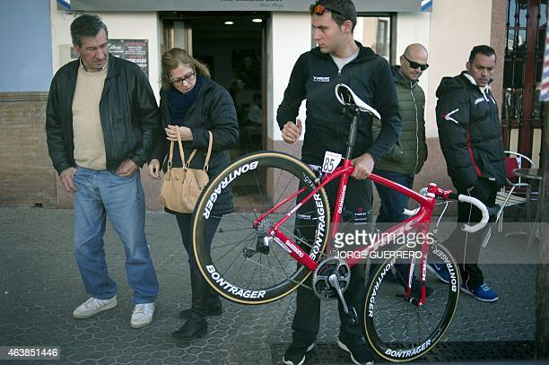 A couple looks at a Trek Factory Racing's mechanic holding a bicycle before the second stage of the 'Ruta del Sol' tour a 1917 km ride from Utrera to...