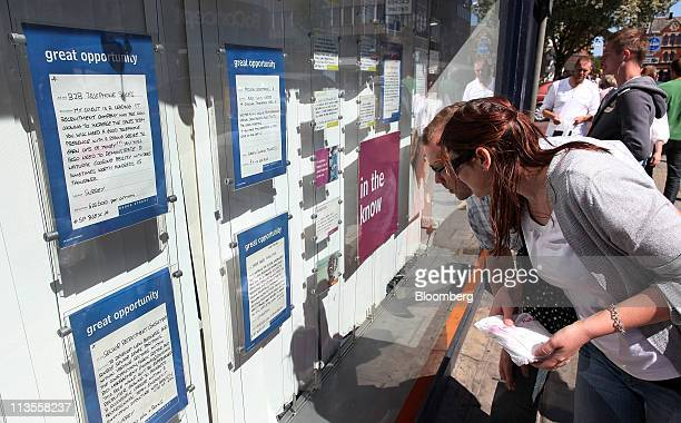 A couple looks at job vacancies on display in the window of a Brook Street employment agency in London UK on Thursday April 28 2011 While the Bank of...