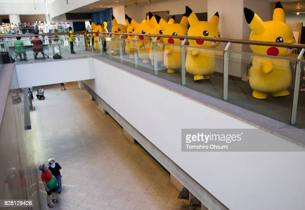 A couple looks at performers dressed as Pikachu a character from Pokemon series game titles marching during the Pikachu Outbreak event hosted by The...