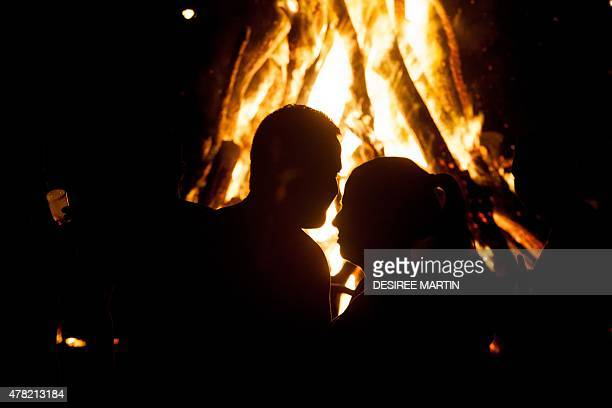 A couple looks at the flames of a bonfire during the traditional Saint John night which coincides with the summer solstice at the beach of Puerto de...