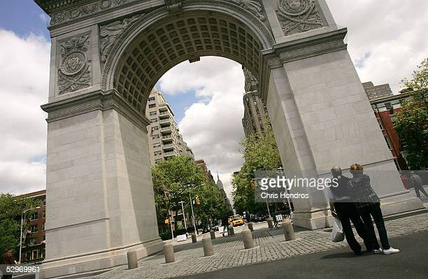 A couple looks at the newly renovated Washington Square Arch in Washington Square Park May 23 2005 in New York City A renovation is planned for the...