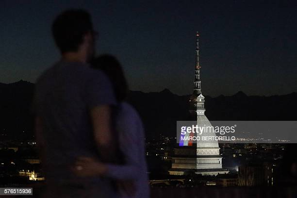 TOPSHOT A couple looks on as the flag of France illuminates the Mole Antonelliana in Turin on July 15 after the deadly attacks in Nice A man drove a...