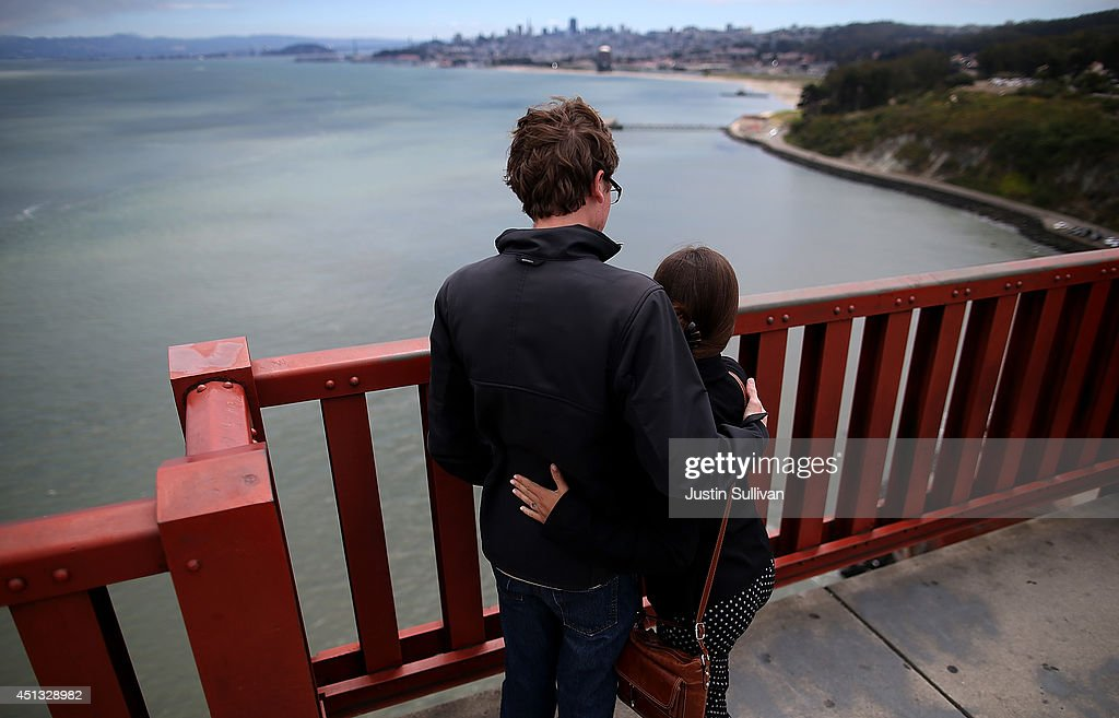A couple looks over the railing on the Golden Gate Bridge on June 27, 2014 in San Francisco, California. The Golden Gate Bridge district's board of directors voted unanimously to approve a $76 million funding package to build a net suicide barrier on the iconic span. Over 1,500 people committed suicide by jumping from the iconic bridge since it opened in 1937. 46 people jumped to their death in 2013.