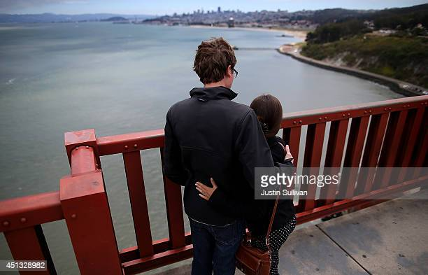A couple looks over the railing on the Golden Gate Bridge on June 27 2014 in San Francisco California The Golden Gate Bridge district's board of...