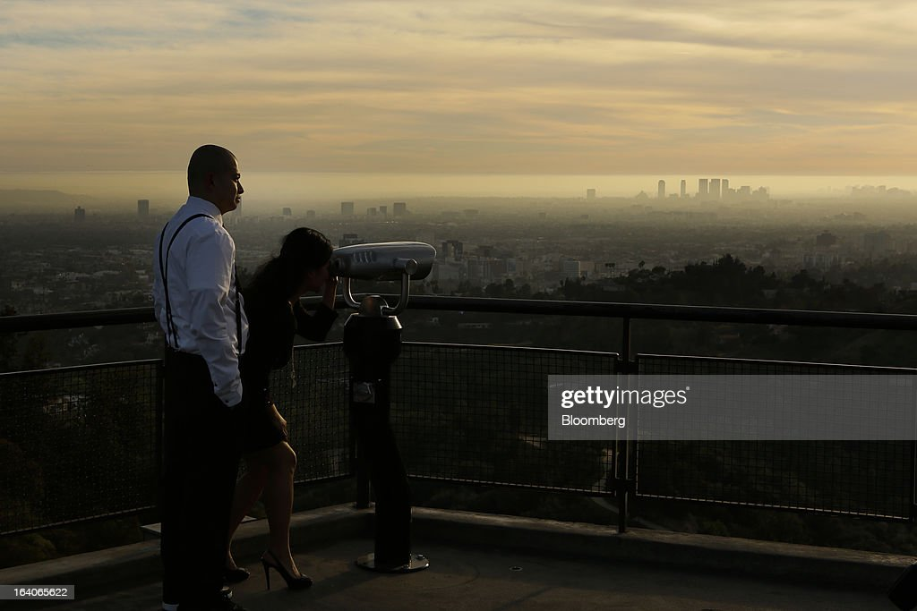 A couple looks through a pair of binoculars towards the sunset from the Griffith Observatory, in Los Angeles, California, U.S., on Thursday, March 14, 2013. California should start a state-run bank to finance economic development that's less polluting and more environmentally friendly, financed by auctions of greenhouse-gas carbon credits, Lieutenant Governor Gavin Newsom said. Photographer: Patrick T. Fallon/Bloomberg via Getty Images