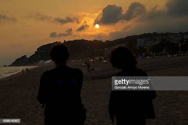 A couple looks to the sunset the day before Ironman Barcelona at Calella beach on October 4 2014 in Calella near Barcelona Spain
