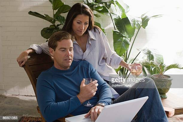 Couple lounging with wine and laptop