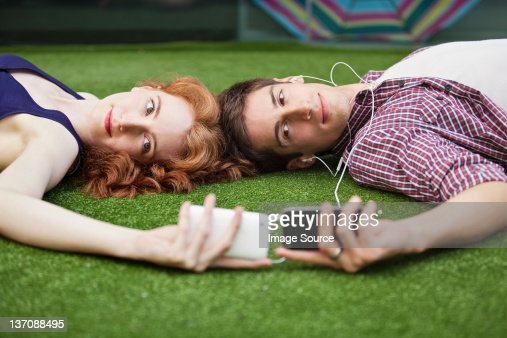 Couple lying down looking at mobile phones : Stock Photo