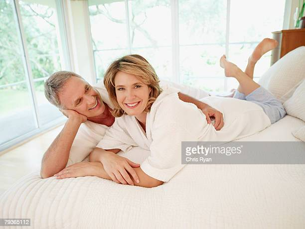 Couple lying in bed being affectionate