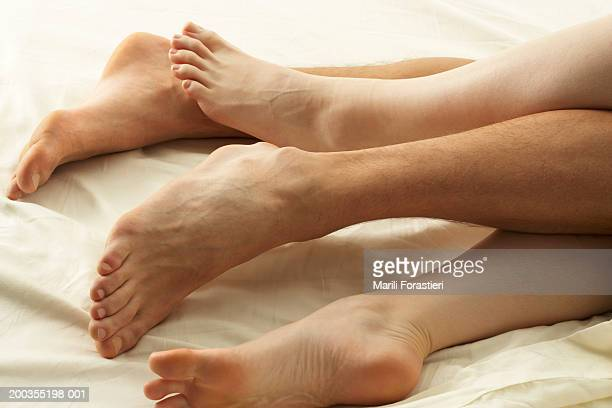 Couple lying in bed, low section, close-up
