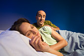 Couple lying in bed, man trying to wake woman